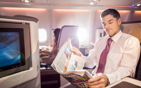 A male passenger in business attire reads the newspaper looking relaxed in the business class cabin