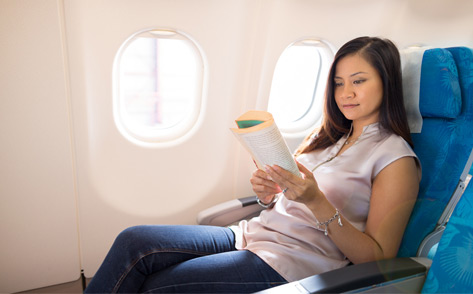 A female passenger stretched out on an extra leg room seat and reading a book
