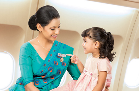 A SriLankan Airlines air hostess holds a smiling girl child pointing at the air hostesses' name tag