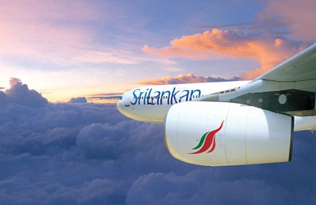 The side view of a SriLankan Airlines plane in flight in the evening sky. The nose of the plane and the engine is visible with SriLankan branding