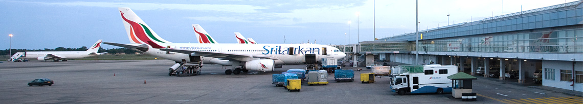 The apron of airport with a row of SriLankan aircraft and the hangar on the right